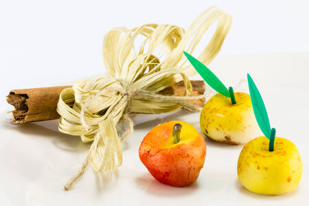 ingradient: red and yellow marzipan apple fruits with cinnamon spicy stick