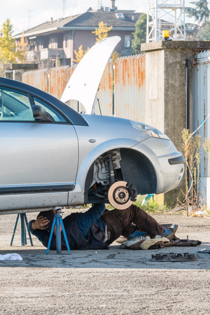 disassembly: Male mechanic working on a car