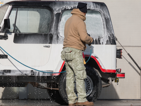 spotless: Man washing his car with a jet of water and shampoo