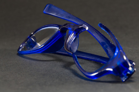vision repair: blue broken glasses on black background