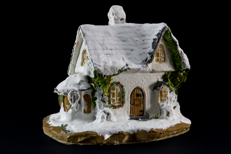 winters: winters christmas decoration with small toy ceramic house over black background