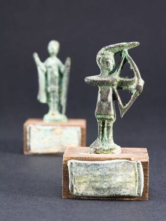 past civilizations: archer bronze statuette and chieftain praying with cloak and stick fgurine Stock Photo