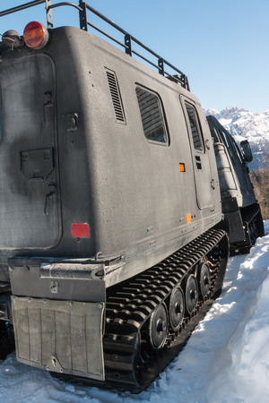 roadless: articulated military tracked cargo vehicle on snow: rear view Editorial