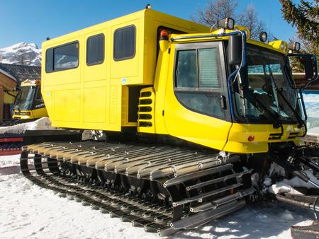 snowcat: yellow tracked vehicle on snow, grooming machine