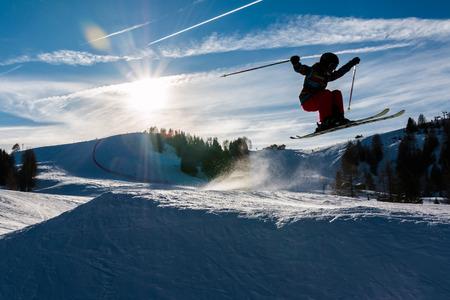 Kleine Skifahrer führt Sprung im Schnee im Skigebiet