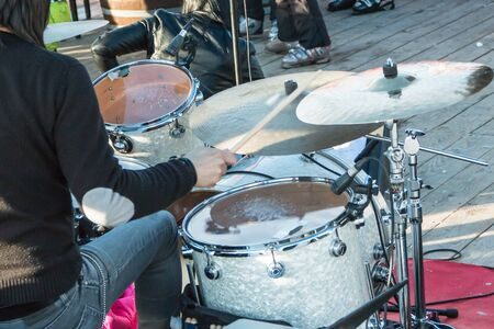 percussionist: black hair drummer during outdoor concert: rear view
