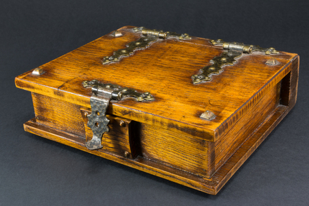 antique woman: wooden brown casket with nail over black background