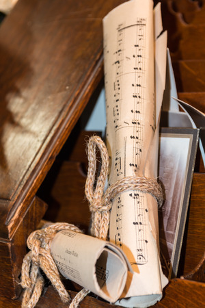 Rolled Music Sheet with aged photo over wooden drawer, composition paper closeup