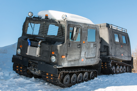 roadless: articulated military tracked cargo vehicle with two units on snow Editorial