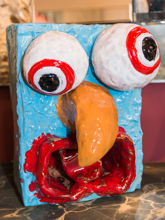 colorful papier-mache sculpture face with orange beak, wonky, cross-eyed and goofy art object