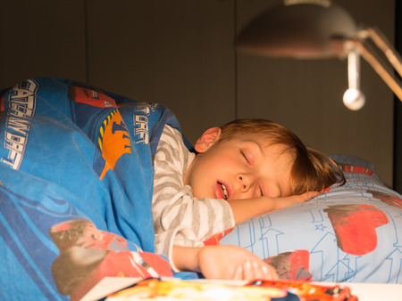 8 Jahre schlafendes Kind auf dem Bett mit einer Bettdecke