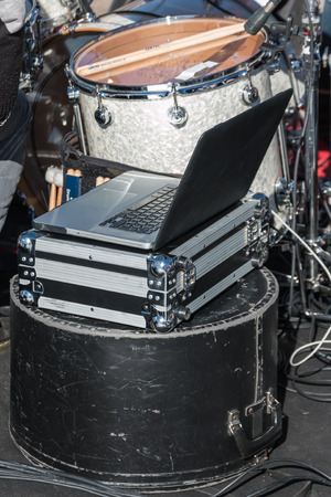 the case before: Pc notebook over metal case and black drum protection cases, rehearsal before show Stock Photo