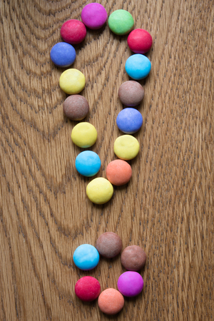 proble: exclamation mark made of coloful praline on wooden background