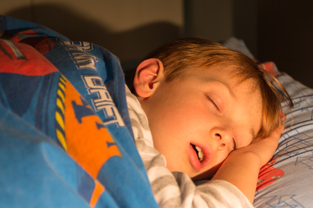 8 years: 8 years sleeping child on the bed with a duvet