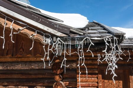 Chalet close-up: gutter with ice and turned off christmas lights Stock Photo