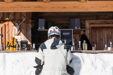 ski lodge: Rear view of woman skiers with helmet waiting at mountain lodge counter for a drink Stock Photo