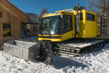 snow grooming machine: yellow tracked vehicle on snow, grooming machine