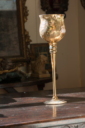 Golden decorated chalice on wooden table and divine light Stock fotó