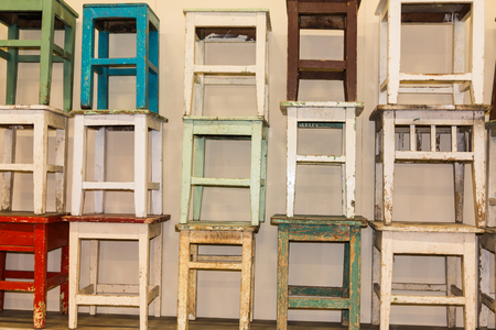timber bench seat: A bunch of worn and colorful stacked stools