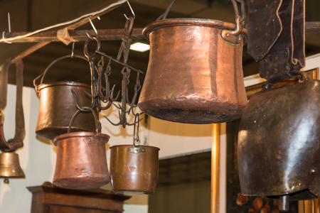 cookware: old copper pots hanged on iron hooks, cookware Stock Photo