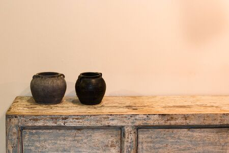 crafted: two empty pots in ethnic style on wooden old-looking cupboard