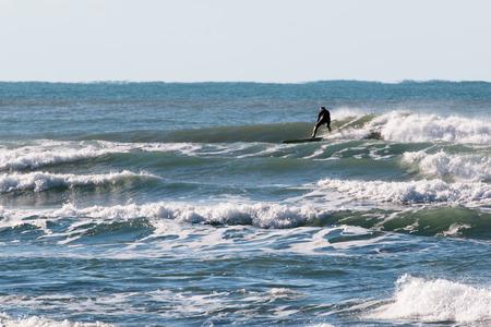 wetsuit: surfer black wetsuit riding the wave