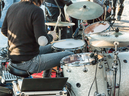 black hair drummer during outdoor concert: rear view