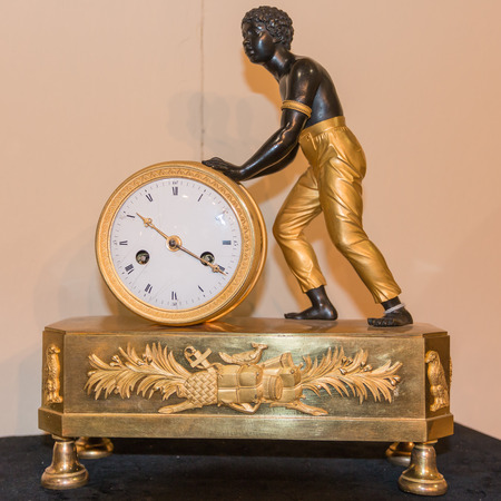 luxurious: Luxurious art objects: ancient clock with slave figurine Stock Photo