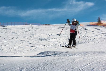 kids at the ski lift: Little skier performs jump in the snow in ski slope