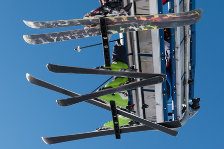 skiers: Skiers on chairlift in mountain