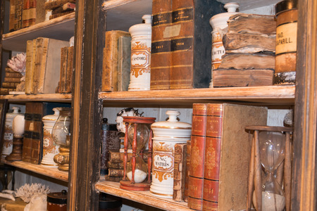 consumed: vintage wooden library with Antique Consumed Books, Ceramic Containers and Hourglass