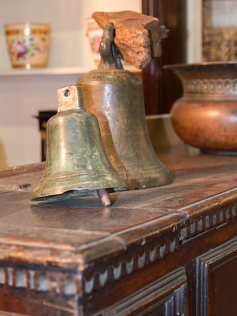 old brazen bells over wooden table