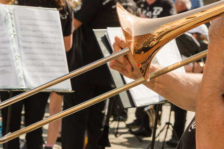 trombone: Brass Trombone, Golden Saxophone in Background during Outdoor Concert