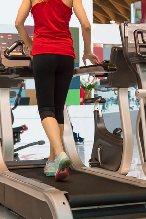 Athletic Young Woman Exercising on a Running Machine in a Fitness Center Archivio Fotografico
