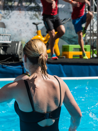 leisure centre: Blonde Hair Woman doing Water Aerobics Fitness in Swimming Pool at the Leisure Centre with Instructors Stock Photo