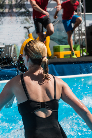 water aerobics: Blonde Hair Woman doing Water Aerobics Fitness in Swimming Pool at the Leisure Centre with Instructors Stock Photo