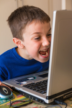 humorously: Joking Child in Front of Touch Screen Laptop, tongue stuck out