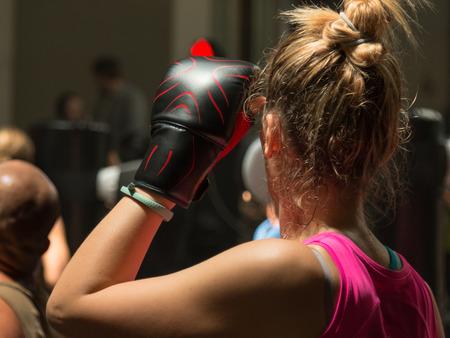 guantes de box: Mujer joven con los guantes de boxeo y Rosa Sportswear en Clase Fitness con Saco Foto de archivo