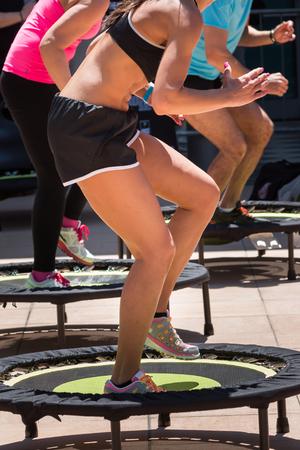 Hübsches Mädchen mit schwarzem Top und Shorts Sportübung auf Rebounder in der Klasse an der Turnhalle in Erwägung