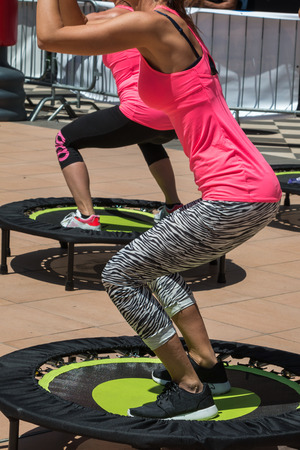 Pretty Girl with Pink Sportswear Having Exercise on Rebounder