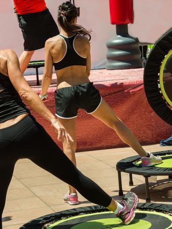 Frauen in Schwarz Sportübung auf Rebounder mit Instructor nach