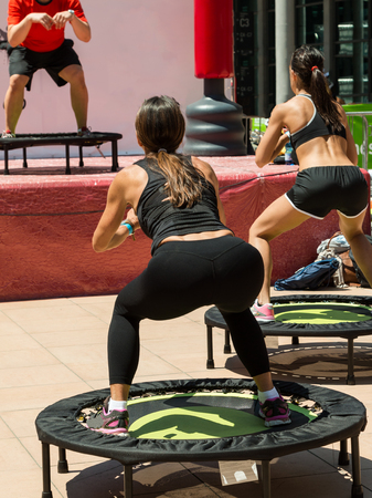 Women in Black Sportswear Having Exercise on Rebounder with Instructor