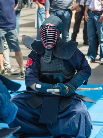 swordsmanship: Kendo Fighter on His Knees match in Traditional Clothes and Bamboo Sword, Japanese Martial Art Stock Photo