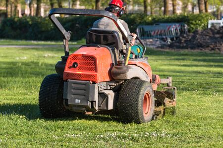 Riding Lawn Equipment with operator for periodically garden upkeep Stock Photo