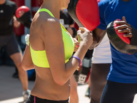 girl fight: American Boy and Caucasian Girl in Sportswear: Fitness and Boxing with Punching Mitts in Outdoor Class at Gym