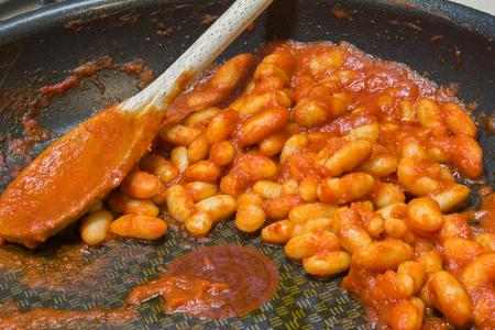 stew pan: Stew Baked Bean in black Frying Pan with Wooden Spoon