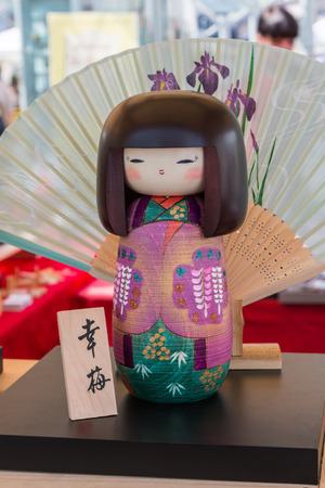 souvenir: Traditional Japanese Wooden Kokeshi Doll and wagasa umbrella in background, Touristic Souvenir Stock Photo