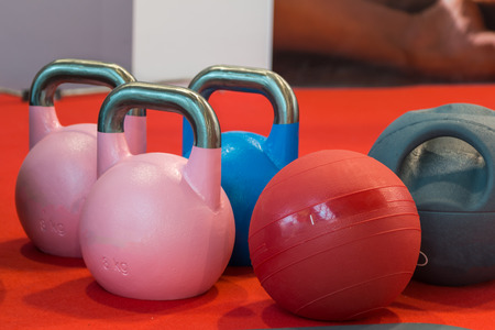 pink and blue rubber kettlebell and medicine ball on red carpet Фото со стока