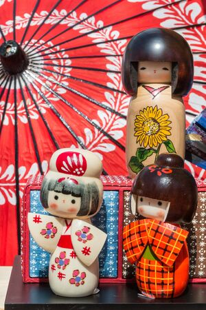 kokeshi: Traditional Japanese Wooden Kokeshi Dolls and wagasa umbrella in background, Touristic Souvenir