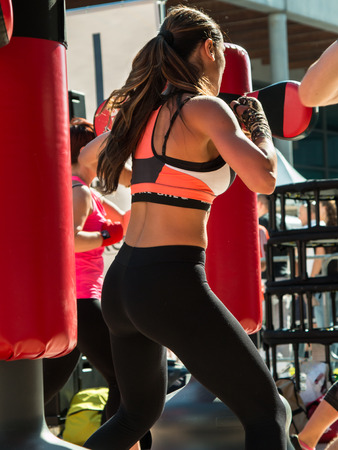 strip club: Young Girl in Fitness Sportswear and Punching Bags, Female Kickboxing Exercise in Outdoor Gym